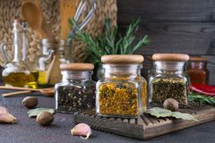 Kitchen utensils, herbs, colorful dry spices in glass jars. On dark  background Stock Photography