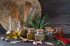Kitchen utensils, herbs, colorful dry spices in glass jars. On dark  background Royalty Free Stock Images