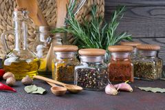 Kitchen utensils, herbs, colorful dry spices in glass jars. On dark  background Stock Photo