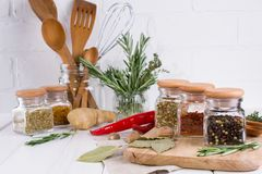 Kitchen utensils, herbs, colorful dry spices in glass jars. On white  background Royalty Free Stock Image