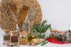 Kitchen utensils, herbs, colorful dry spices in glass jars. On white  background Stock Images