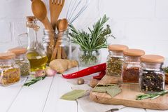 Kitchen utensils, herbs, colorful dry spices in glass jars. On white  background Stock Photo