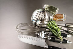 Kitchen utensils and herbs on stainless steel Royalty Free Stock Photos