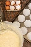 Kitchen utensils, ingredients and batter. Kitchen utensils, ingredient and cake batter in bowl next to a baking tray lined with cup cake paper cups Stock Photography