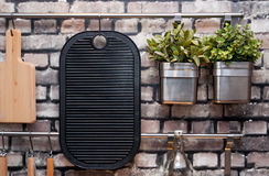 Kitchen utensils. Modern kitchen details - steel pots with growing herbs, cutting board and other utensils stock images
