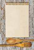 Kitchen utensils and paper spiral notebook on the old wood. Rustic background Royalty Free Stock Photography