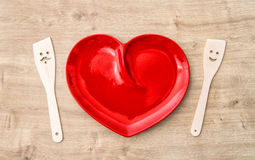 Kitchen utensils red plate. Cooking with love Royalty Free Stock Image