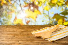 Kitchen utensils and tablecloth on wooden table over autumn bokeh background