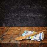 Kitchen utensils on tablecloth on wooden textures table against chalkboard background Stock Image