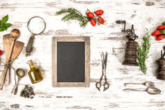 Kitchen utensils with tomatoes, herbs and blackboard Royalty Free Stock Images