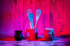Kitchen utensils on wooden blue red purple gradient background. Close up Royalty Free Stock Image