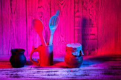 Kitchen utensils on wooden blue red purple gradient background. Close up Stock Images