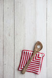 Kitchen Utensils: Wooden Spoon and Potholder on White Wooden Bac Stock Photo