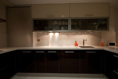 Kitchen V. Modern kitchen with cream and chocolate cupboards and steel hood royalty free stock photography