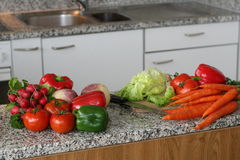 Kitchen with vegetables. Kitchen composition with fresh vegetables on work table, with sink and cooking facilities in the background Royalty Free Stock Photo