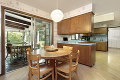 Kitchen with view into sunroom. Kitchen in suburban home with view to sunroom stock photos