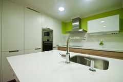 Kitchen Vigo. Modern kitchen with white and wood cupboards and steel hood royalty free stock photography