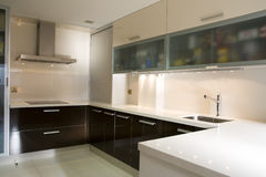 Kitchen VII. Modern kitchen with cream and chocolate cupboards and inox hood Royalty Free Stock Images
