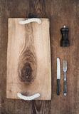 Kitchen-ware set. Old rustic serving board tray, knive and fork, pepperbox on a old wooden background. Top view Royalty Free Stock Photos
