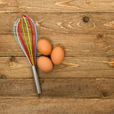 Kitchen whisk and eggs Royalty Free Stock Image