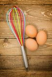 Kitchen whisk and eggs Royalty Free Stock Photography