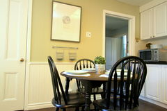 Kitchen with white cabinets and round table and chairs Royalty Free Stock Photos