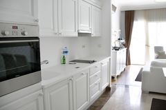The kitchen is white with white cupboards, stove, refrigerator, sink. White room. Apartments. A room with a white sofa, in the brightest interior stock photo