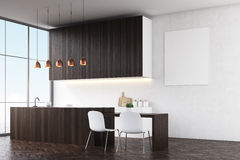 Kitchen with white walls, dark wooden counters and white chairs near a dining table. Royalty Free Stock Photography
