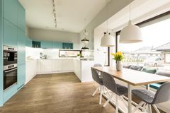 Kitchen with window. White and blue kitchen interior with big dining table, chairs and window stock photo