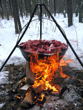 Kitchen in the winter forest. Wild boar cooked on fire in a VAT, the opening day of hunting Stock Image