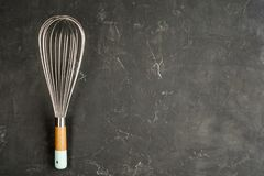 Kitchen Wire Whisk Eggs Beater on the dark concrete background with copy space. Flat lay background. stock images