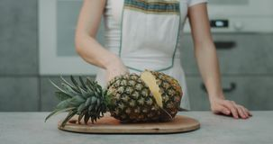 In the kitchen a woman cut a big pineapple with a big knife closeup, slow motion.