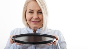 Kitchen woman gives empty black plate for your advertising products isolated on white background. Mock up for use royalty free stock photography