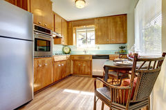 Kitchen with wood cabinets and chair. Royalty Free Stock Images