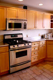 Kitchen wood cabinets stainless stove. New kitchen with wood cabinets, stainless steel stove and laminate counter top refrigerator Stock Photo