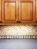 Kitchen with wooden cabinets and tile decor Royalty Free Stock Photo