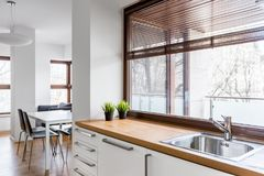 Kitchen with wooden countertop. White kitchen with wooden countertop, silver sink and big window with blinds royalty free stock images