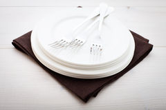 Kitchen. Wooden table with empty plate, tablecloth for dinner. Royalty Free Stock Image