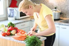 Kitchen work. Young woman is in the kitchen making salad royalty free stock photos