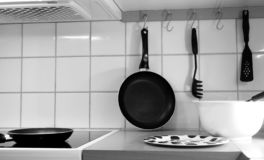 Kitchen work zone with tools, bowl and frying pans, in black and white. royalty free stock photos