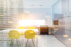 Kitchen with yellow chairs double. White kitchen interior with a narrow window, a table with built in shelves, a row of counter top, yellow chairs and two ovens Royalty Free Stock Photo