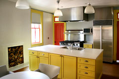 Kitchen yellow wood cabinets  stainless stove. New kitchen with yellow wood cabinets, black and stainless steel stove and island Royalty Free Stock Images
