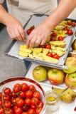 Kitchener põe fatias da batata com tomates e as especiarias frescos sobre a bandeja Imagem de Stock