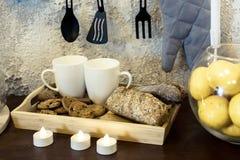 kitchenware Δύο άσπρες κούπες καφέ σε έναν πίνακα μπροστά από έναν συμπαγή τοίχο Οι κούπες είναι σε έναν δίσκο με το ψωμί κεριά η στοκ φωτογραφία