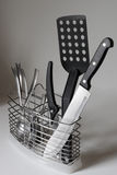 Kitchenware. Kitchen khifes, spons, forks and spatula in steel container Stock Photography