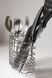 Kitchenware. Kitchen khifes, spons, forks and spatula in steel container Stock Photos