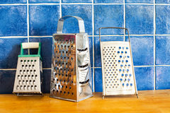 Kitchenware accessories. stainless steel graters on wooden board. blue tiled background Stock Image