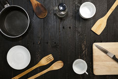 Kitchenware on the black wooden background. Royalty Free Stock Images