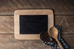 Kitchenware on a blackboard with a blue checkered napkin. On wooden table Royalty Free Stock Photo