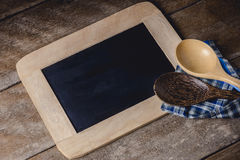 Kitchenware on a blackboard with a blue checkered napkin. On wooden table Royalty Free Stock Image